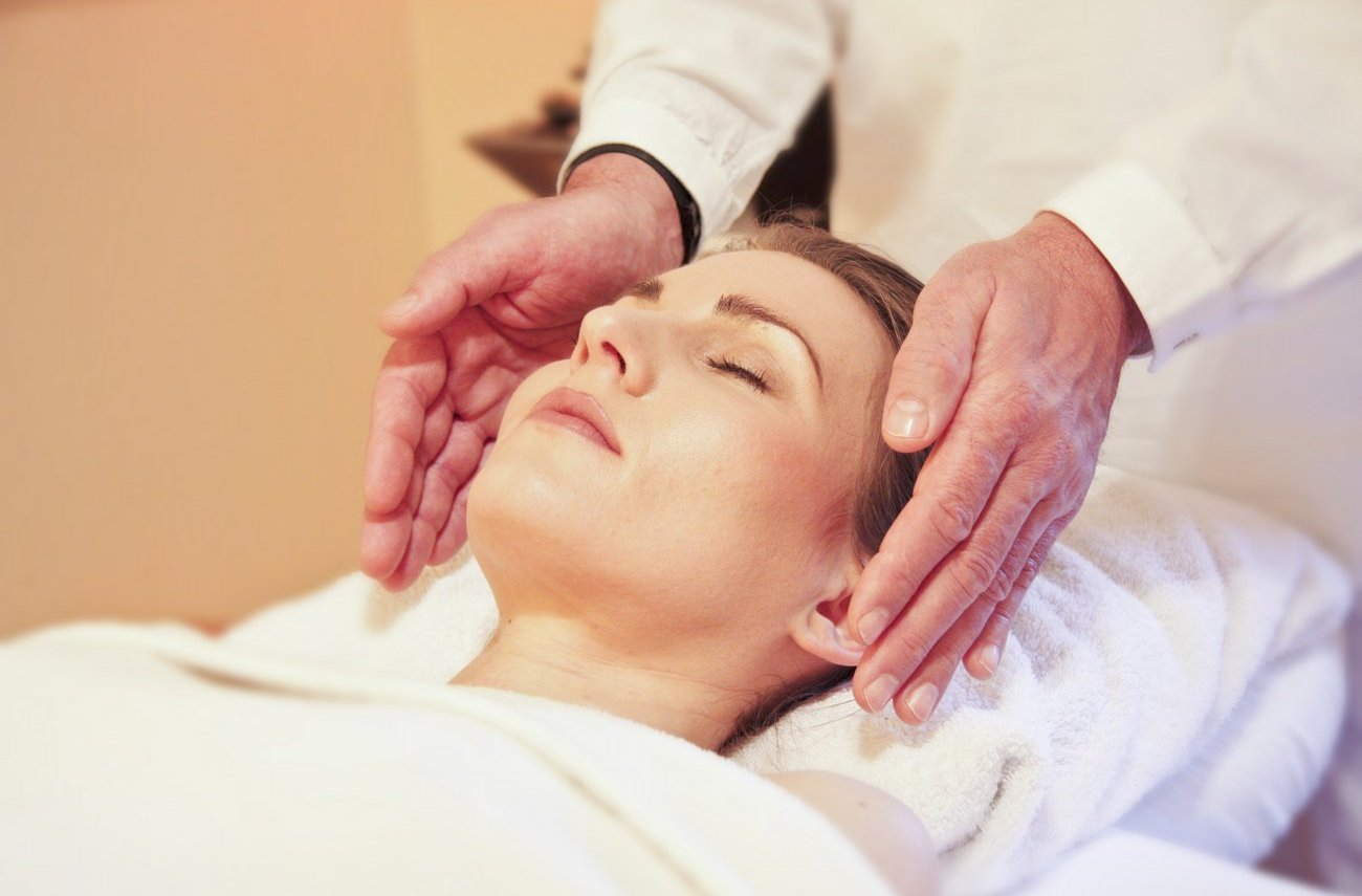 Reiki practicioner performing reiki on woman's head